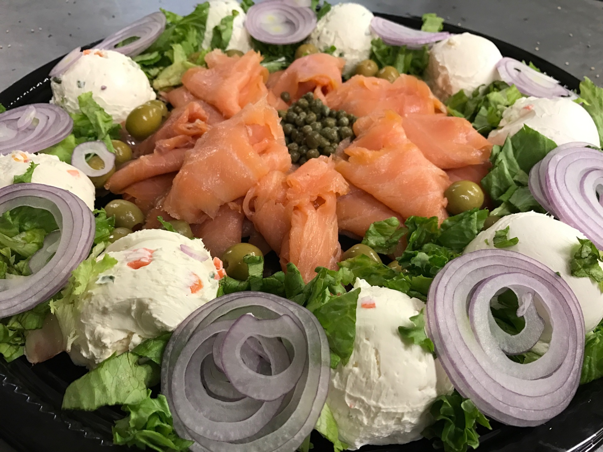 A platter of lox, onions, capers, and cream cheese.